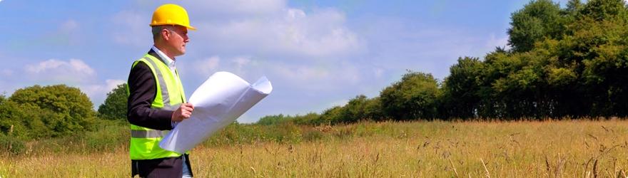 Man wearing a hard hat, walking through a field